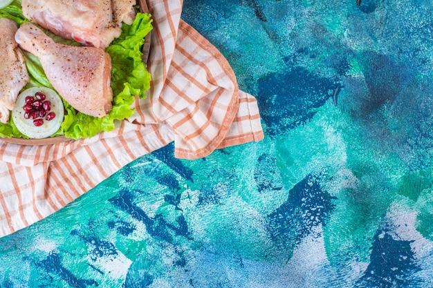 Hühnerfleisch, zitrone, granatapfelkerne auf einer holzplatte auf dem geschirrtuch