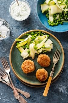 Hühnerfleischbällchen mit zucchinisalat und erbsen, mit knoblauch-joghurt-sauce.