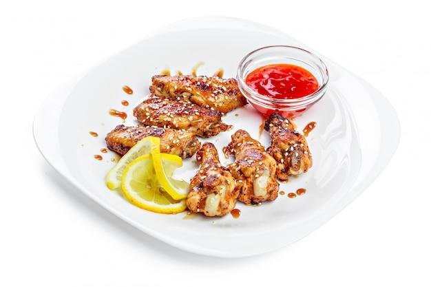 Hühnerflügel auf platte mit soße