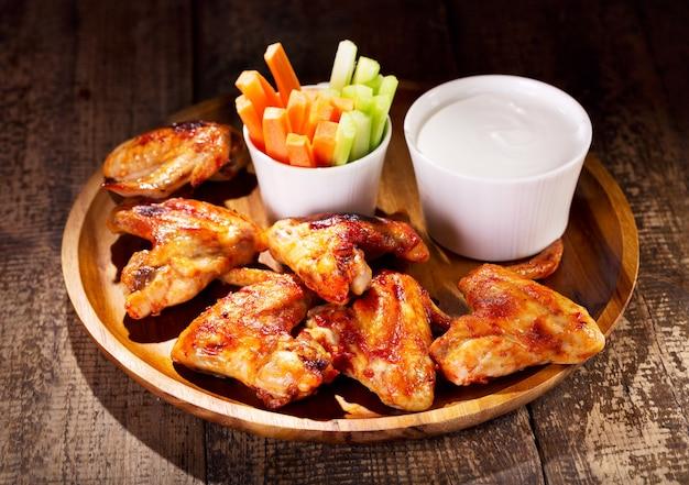 Hühnerflügel mit frischem gemüse und soße auf holztisch