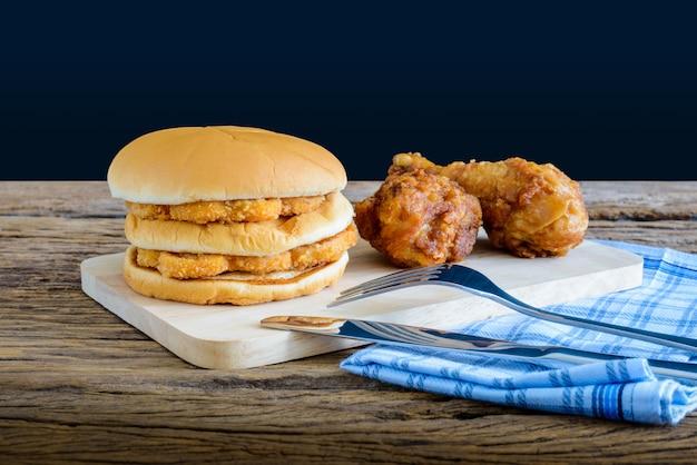 Hühnerhamburger und gebratenes huhn auf hölzernem schneidebrett mit messer und gabel, serviette
