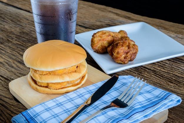 Hühnerhamburger und gebratenes huhn, glas cola auf hölzernem schneidebrett mit messer, für