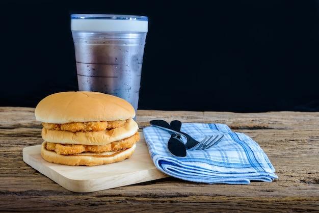 Hühnerhamburger und glas kolabaum auf hölzernem schneidebrett mit messer und gabel