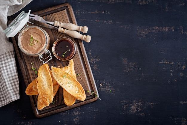 Hühnerhausgemachte leberpastete im glas mit toast und preiselbeermarmelade mit paprika.