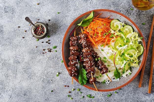 Hühnerherzen in pikanter soße, nudeln und gemüsesalat. gesundes essen. draufsicht