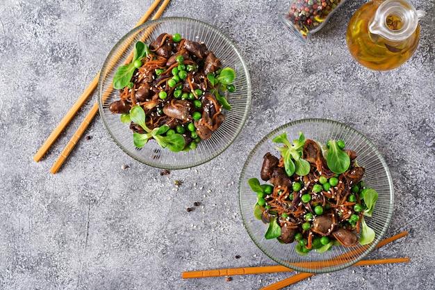 Hühnerherzen mit karotten, zwiebeln und grünen erbsen im asiatischen stil. draufsicht