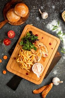 Hühnerhieb und pommes-frites auf einem hölzernen brett