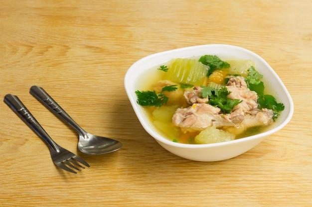 Hühnerklare suppe in der weißen schüssel auf holztisch