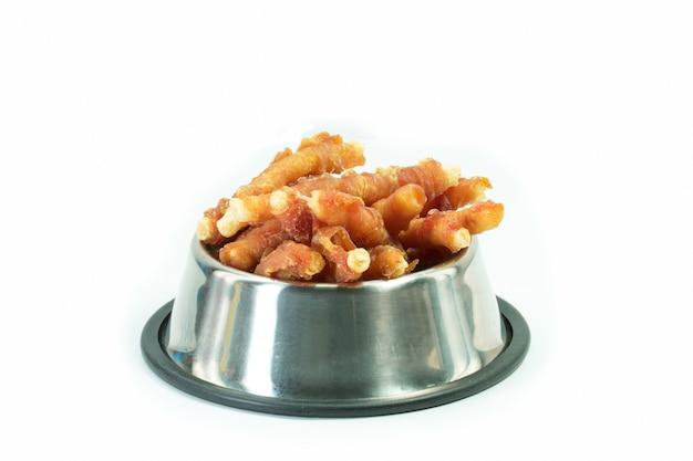 Hühnerknochen in der rostfreien schüssel für den hund lokalisiert. snack für haustiere konzept.