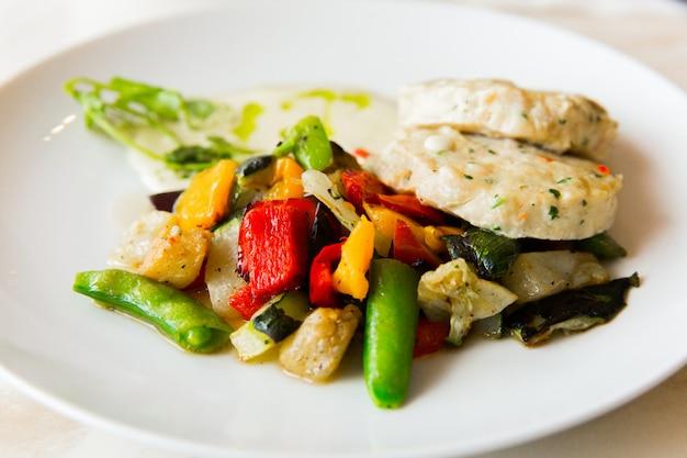 Hühnerkoteletts mit gemüse in der weißen platte auf weißer tabelle im restaurant