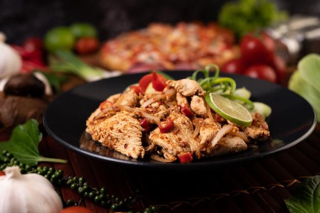 Hühnerlarb auf dem teller mit getrockneten chilis, tomaten, frühlingszwiebeln und salat