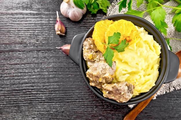Hühnerleber gedünstet mit orangen, sauerrahm, sojasauce und provence-kräutern in einer kleinen pfanne mit kartoffelpüree auf sackleinenserviette, einem löffel und petersilie auf holzbretthintergrund von oben