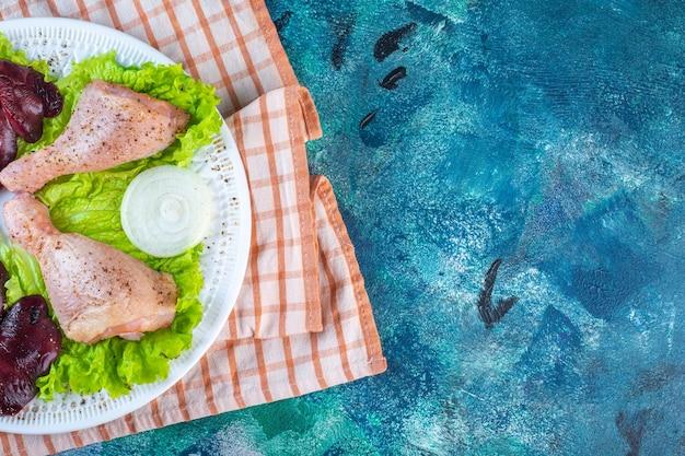 Hühnerleber, salatblätter und hühnerkeule auf einem teller auf dem geschirrtuch