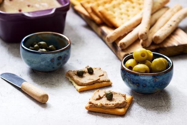 Hühnerleber, zwiebel und karottenpaste, serviert mit crackern, grissini, oliven, kapern und champagner.