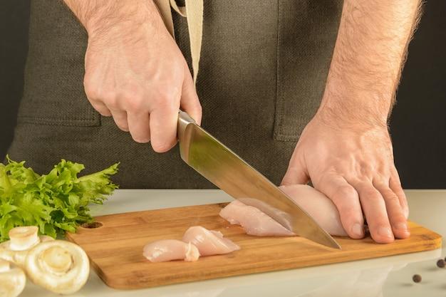 Hühnermachen ein mann in einem schutzblech schneidet fleisch auf einem hölzernen brett.