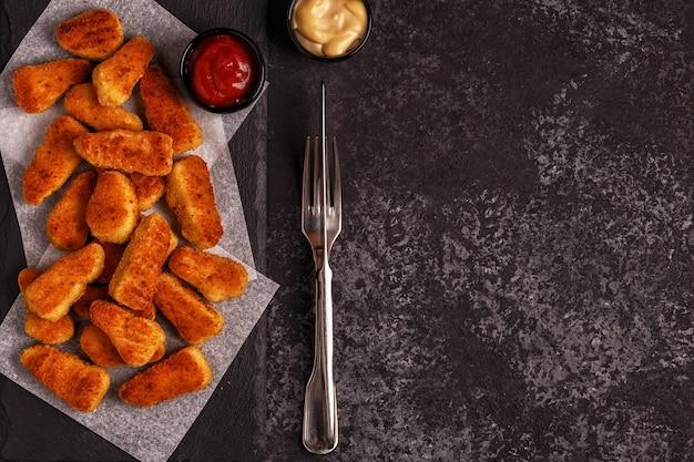 Hühnernaggets mit saucen im dunkeln