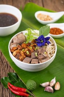 Hühnernudeln in einer schüssel mit beilagen, thailändisches essen