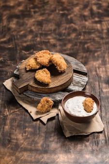 Hühnernuggets auf einem holzbrett mit weißer sahnesauce