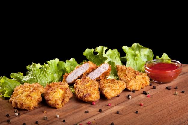 Hühnernuggets, auf einem holztisch mit soße und kopfsalat auf schwarzem hintergrund.