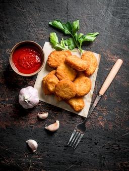 Hühnernuggets auf papier mit knoblauchzehen, soße und petersilie auf dunklem rustikalem tisch