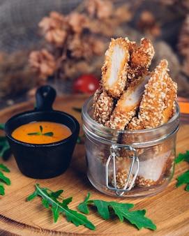 Hühnernuggets frittiert mit sesam mit käsesauce und rucola. restaurant servieren.