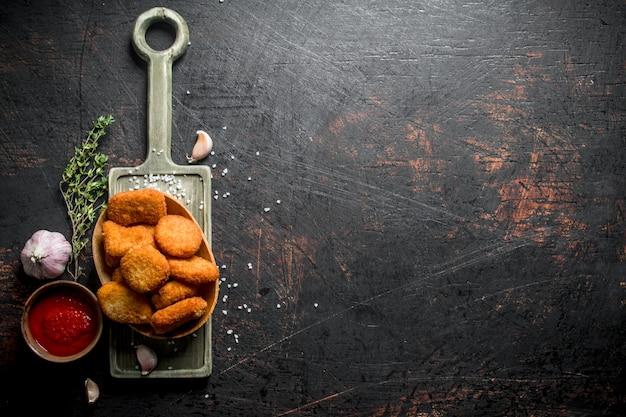 Hühnernuggets in einer schüssel mit thymian, knoblauch und soße auf dunklem holztisch