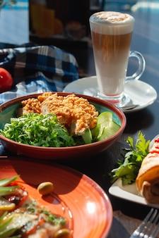 Hühnernuggets in einer tonplatte mit gemüse und gurke am buffet