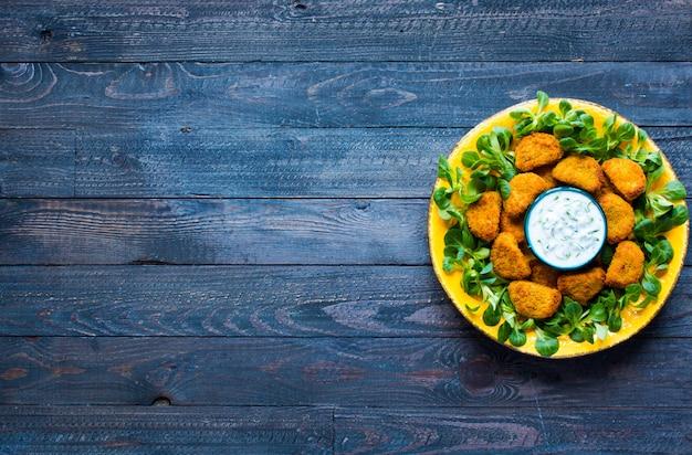 Hühnernuggets mit jogurtsoße auf einem hölzernen hintergrund