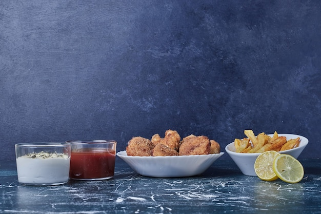 Hühnernuggets mit kartoffeln und saucen in weißen tellern.