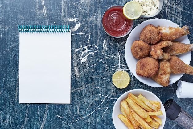Hühnernuggets mit kartoffeln und saucen mit einem notizbuch beiseite.