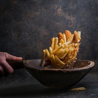 Hühnernuggets mit pommes frites und menschlicher hand in der fliege