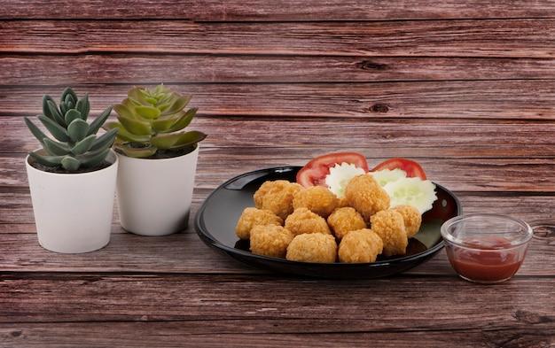 Hühnernuggets mit salat und tomatensauce neben kaktus