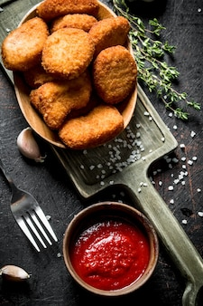 Hühnernuggets mit sauce und thymian auf holztisch