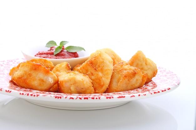 Hühnernuggets mit tomatensauce auf einer platte