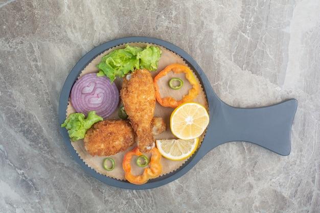 Hühnernuggets mit zitrone und zwiebel auf dunkler pfanne