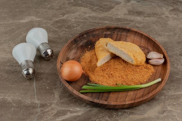 Hühnernuggets mit zitrone, zwei knoblauchzehen und zwiebeln auf holzbrett mit salz und pfeffer.