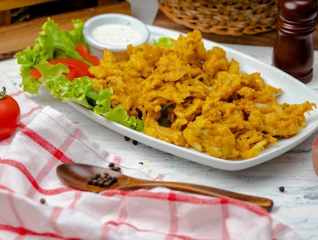 Hühnernuggets serviert mit mayonnaise-joghurtsauce in einer weißen platte mit salat und tomaten