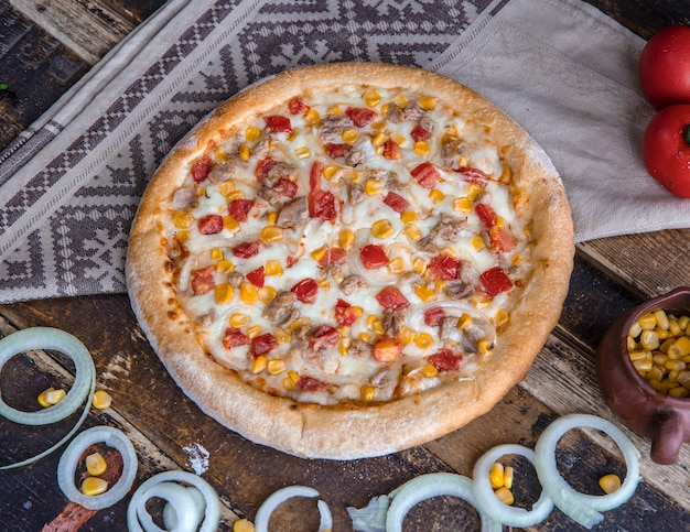 Hühnerpizza mit tomaten, zwiebeln und ranch sauce auf dem holztisch