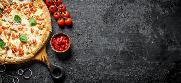Hühnerpizza und tomatenmark in der schüssel auf schwarzem holztisch