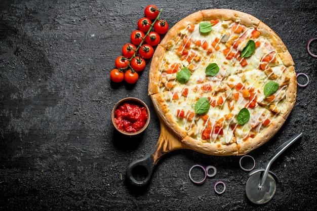 Hühnerpizza und tomatenmark in der schüssel auf schwarzem rustikalem tisch