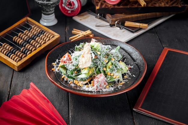 Hühnersalat mit salat und pinienkernen mit geriebenem parmesan bestreut