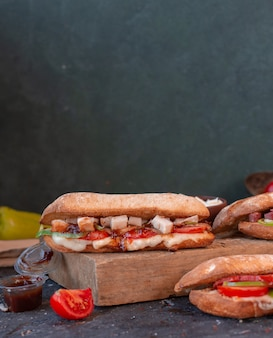 Hühnersandwich mit fetawürfeln im stangenbrot auf einem hölzernen brett