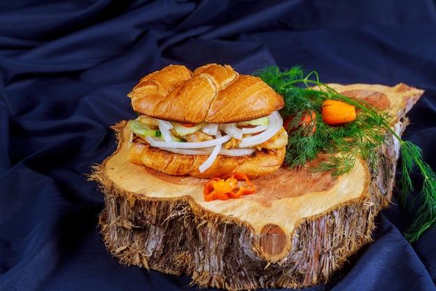 Hühnersandwich mit zwiebeltomatengurke auf einem hölzernen stand