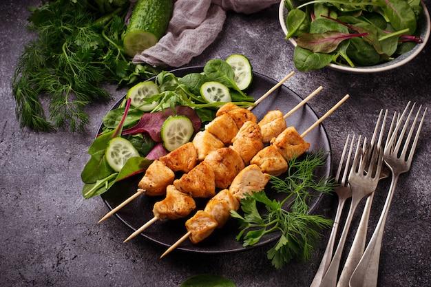 Hühnerschaschenkebabs mit grünem salat. selektiver fokus