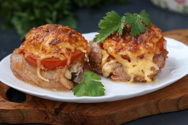 Hühnerschenkel mit tomaten und käse vereinbarten in einer platte auf einem hölzernen brett