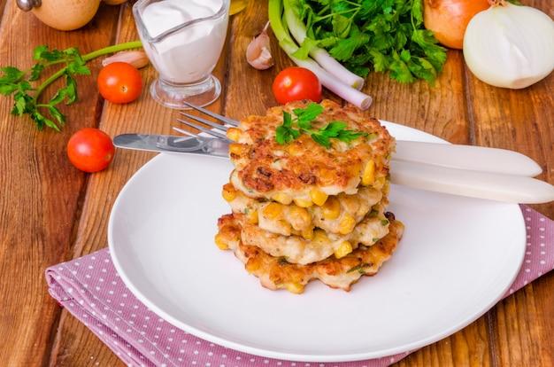 Hühnerstückchen mit mais, zwiebeln und frischen kräutern