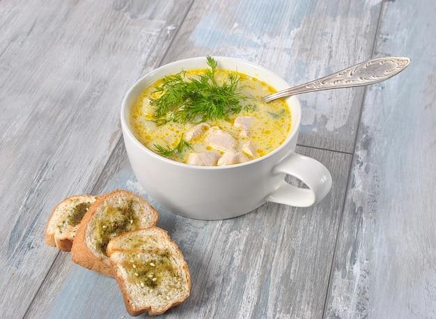 Hühnersuppe. heiße wintersuppe mit hühnchen und kartoffeln. chowder-suppe mit huhn und kartoffeln. frische cremige suppe mit huhn und gemüse in der weißen schüssel auf dem hölzernen hintergrund. gesundes essen