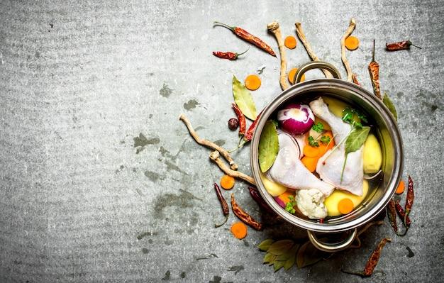Hühnersuppe mit gemüse in einem großen topf kochen. auf dem steintisch.