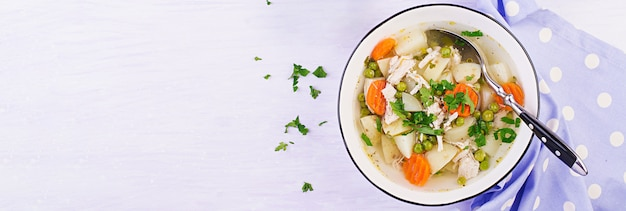Hühnersuppe mit grünen erbsen, karotten und kartoffeln in einer weißen schüssel