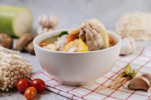Hühnersuppe mit mais, shiitake-pilz, enoki-pilz und karotte.